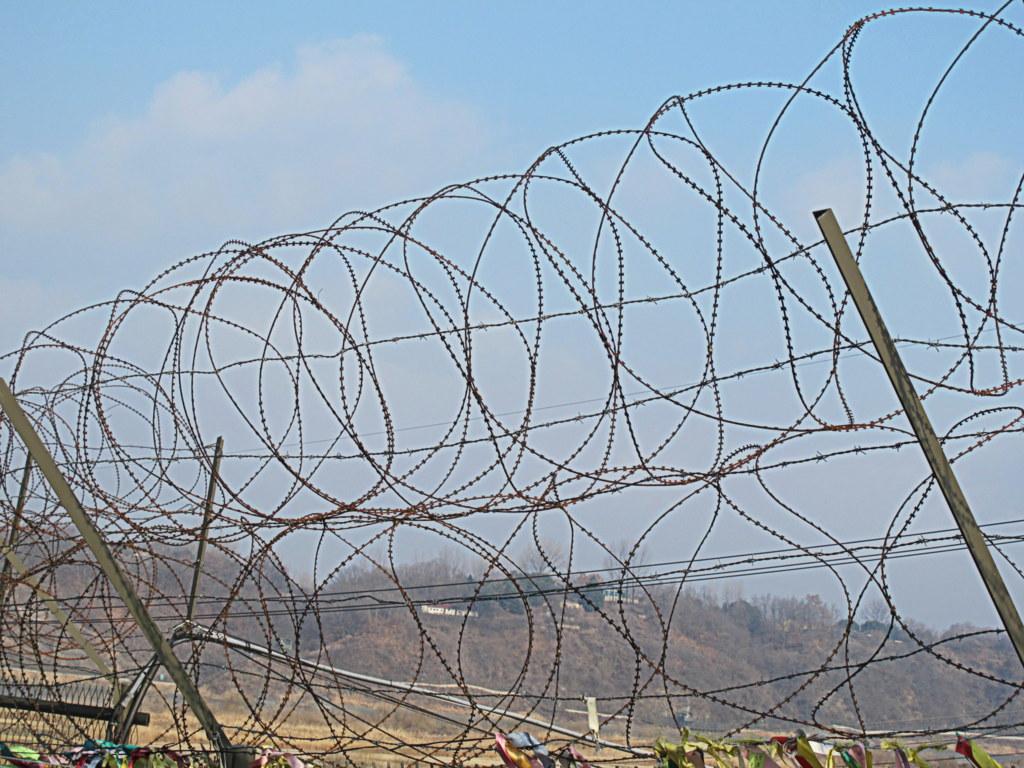 Stacheldraht an der Grenze von Nord- und Südkorea. das Bild kennt man auch aus anderen Gegenden der Welt.
