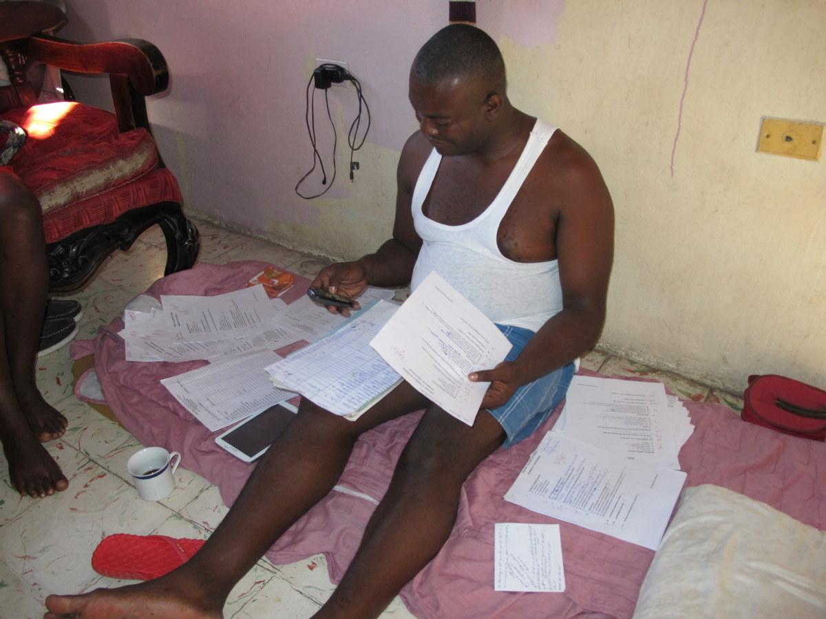 Emmanuel ist Lehrer. Hier korrigiert er Schularbeiten.
