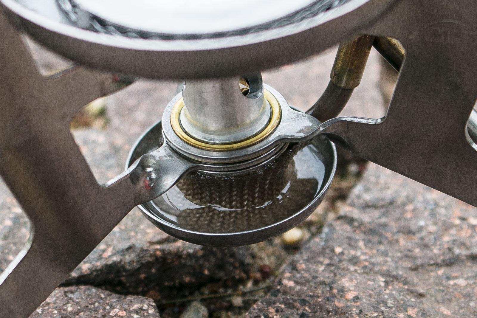 Der Ring unter dem Kocher muss ein wenig mit Benzin befüllt werden. Dieses muss abrennen um den Kocher vorzuwärmen.