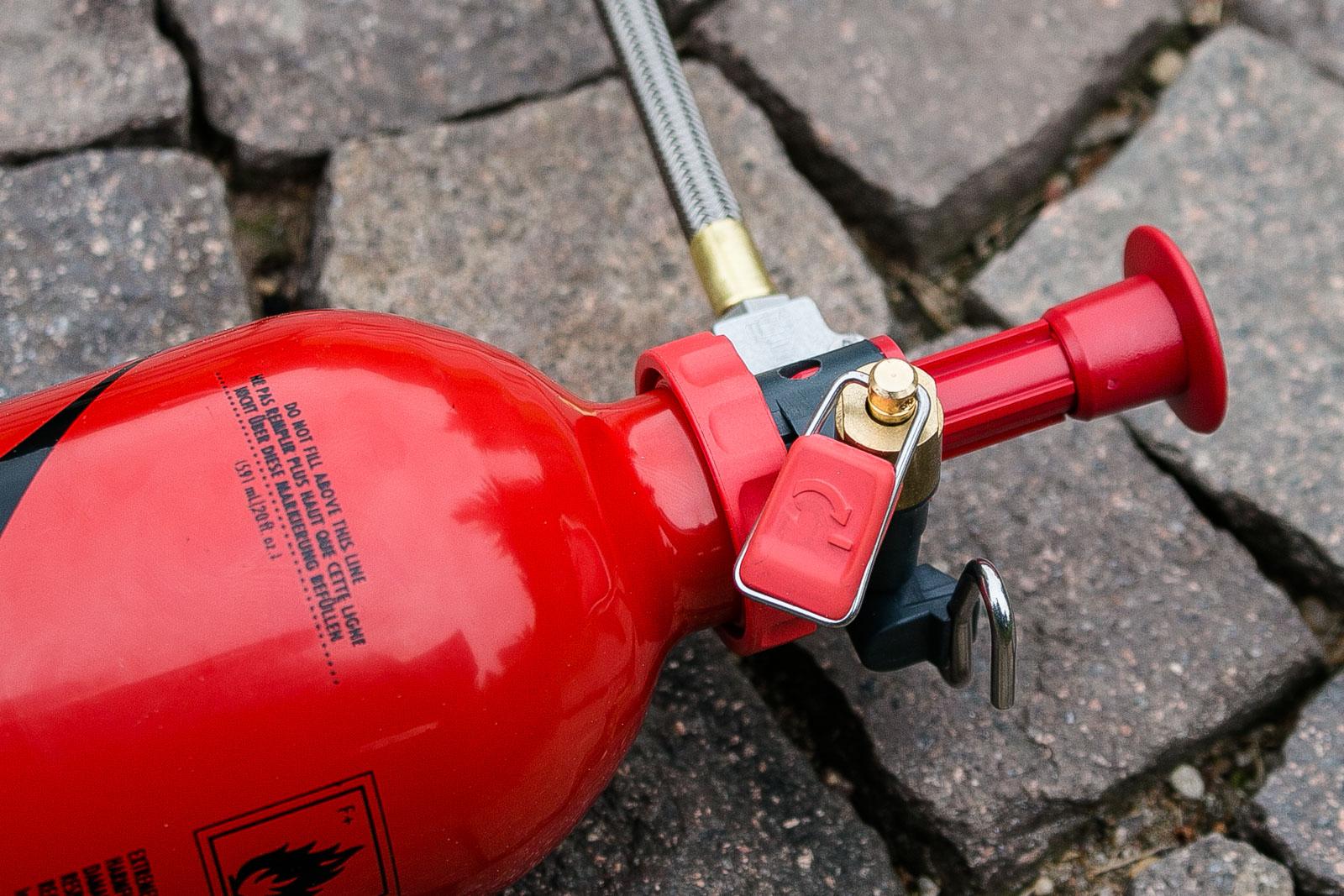 Die Brennstoffflasche des Whisperlite mit der dazugehörigen Pumpe, dem Ventil und der Kraftstoffleitung. Das Ventil muss für den Betrieb jeweils mehr oder weniger stark geöffnet werden.
